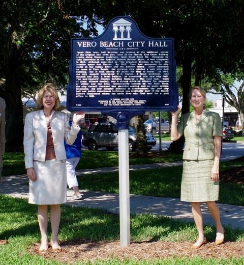 Two women standing by City Hall dedication sign